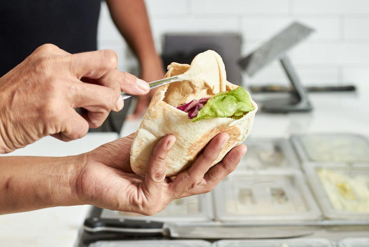Building a pita sandwich at Falafel, Inc.