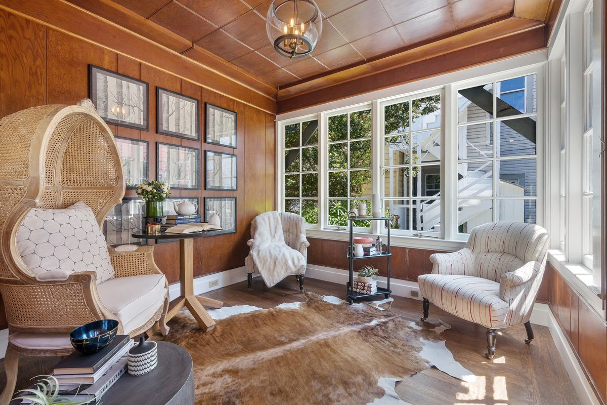 The living room walls and ceiling are decked out in wood paneling. The windows are white and large. The floors are hardwood.