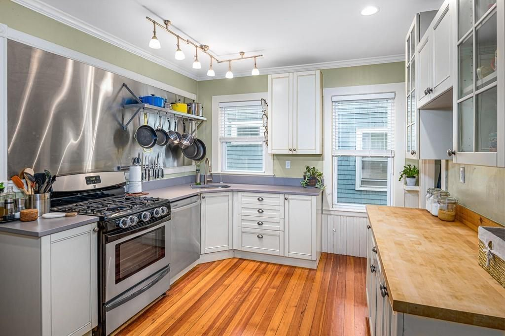 A kitchen with two counters and pots and pans hanging from a rack.