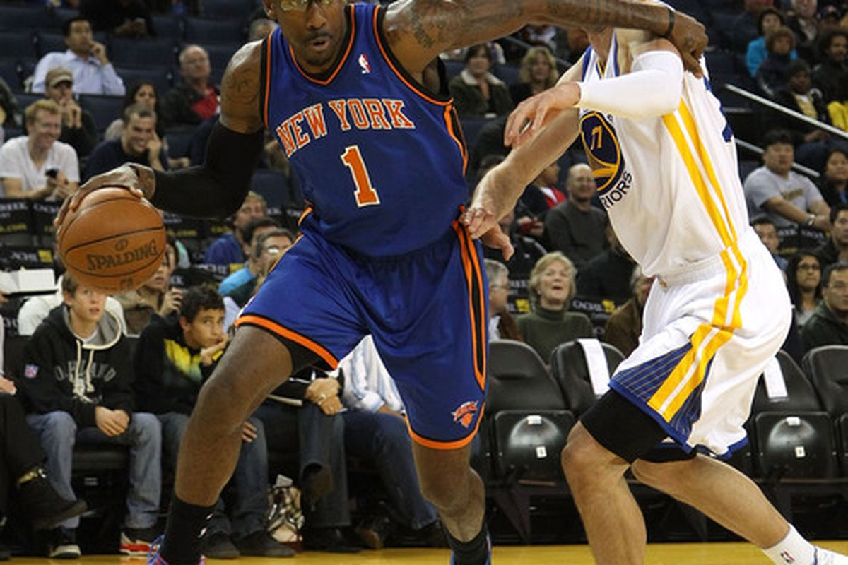 Amar'e Stoudemire (1) of the New York Knicks dribbles past Vladimir Radmanovic (77) of the Golden State Warriors at Oracle Arena on November 19 2010 in Oakland California.  (Photo by Ezra Shaw/Getty Images)