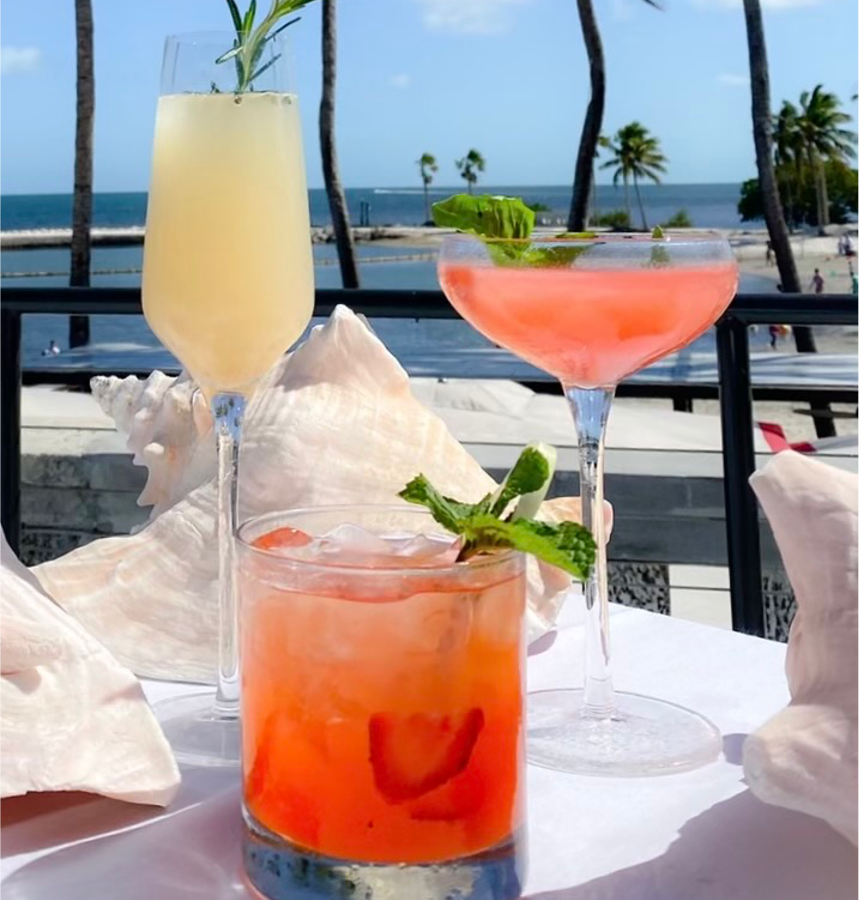 Three cocktails: one yellow, one pink and one orange topped with herbs and a view of the water