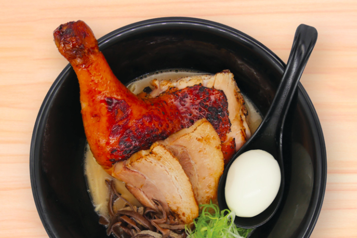 A bowl of ramen from Koo Ramen in LA with a whole chicken leg, boiled egg, and chashu pork pieces