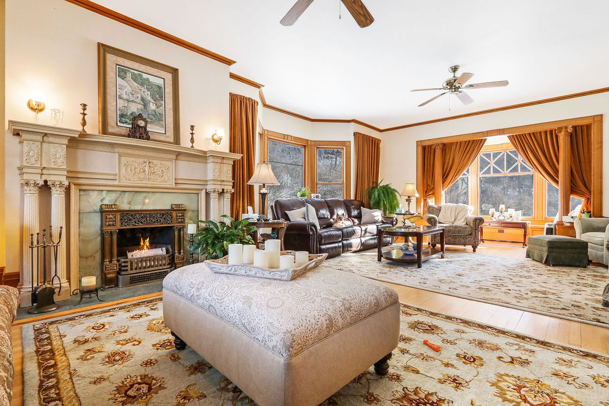 A large living room has multiple couches, rugs, a fireplace, and wood floors.