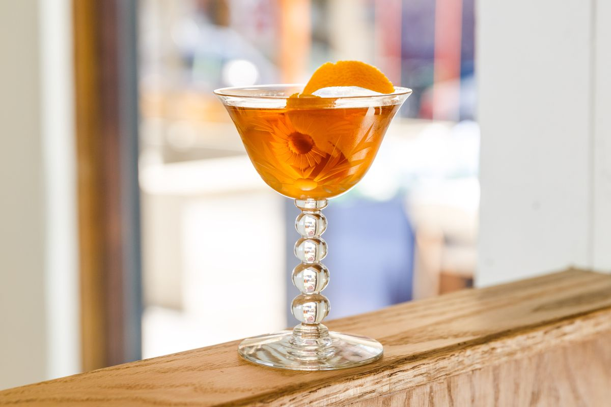 A decorated glass filled with orange liquid and a slice of orange peel for garnish