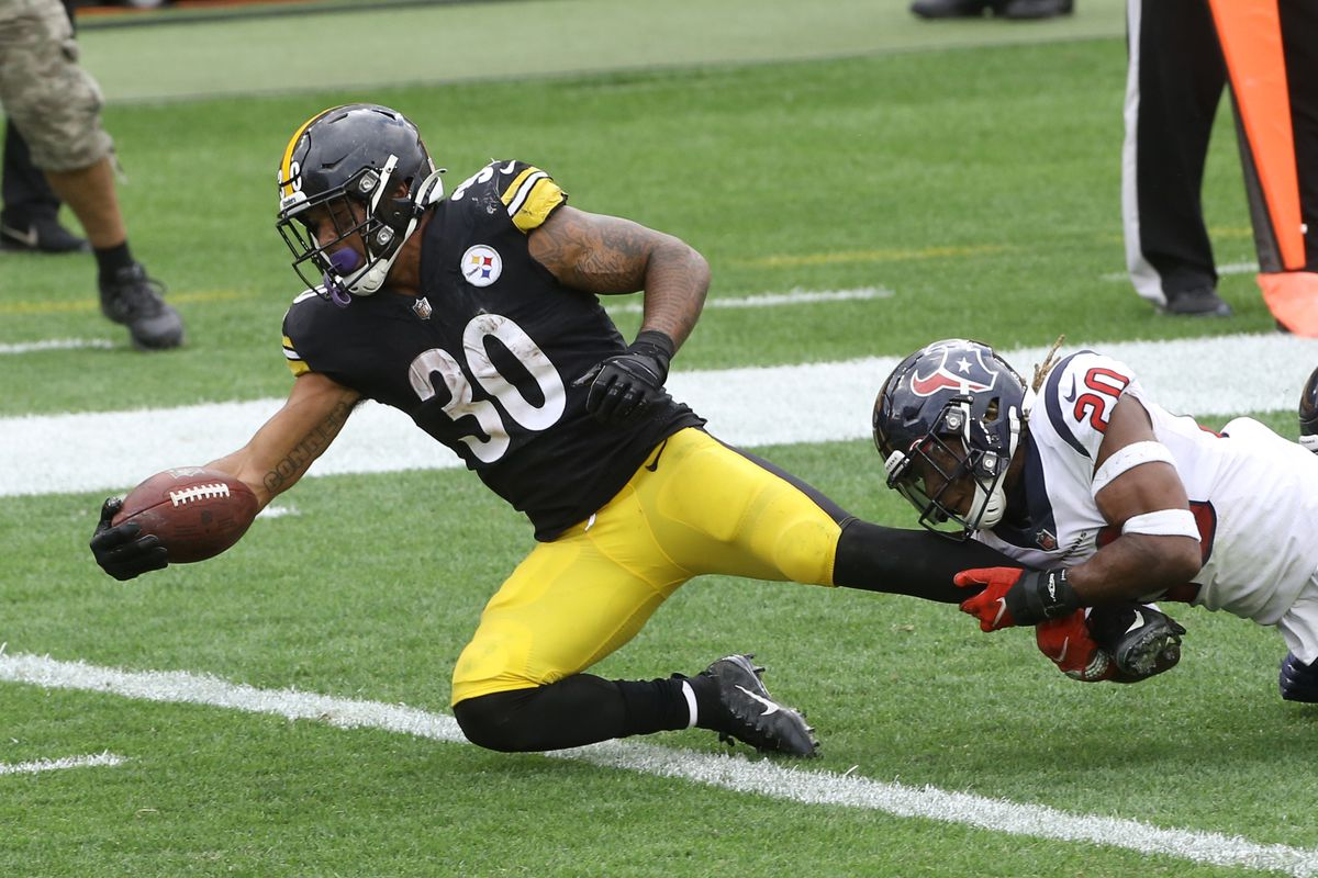 Pittsburgh Steelers running back James Conner (30) reaches the ball over the goal line for the game winning touchdown as Houston Texans strong safety Justin Reid (20) defends during the fourth quarter at Heinz Field.