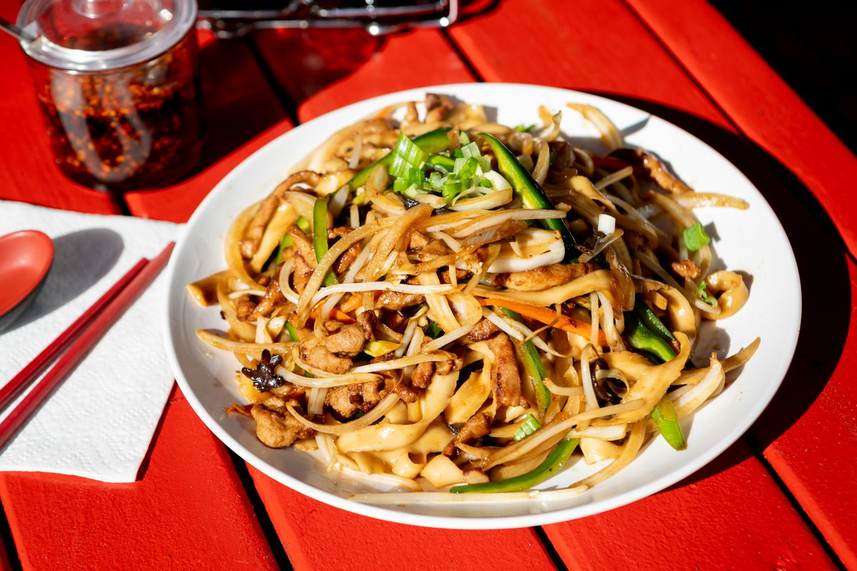 A plate of knife-cut noodles topped with pork and green bell pepper slices