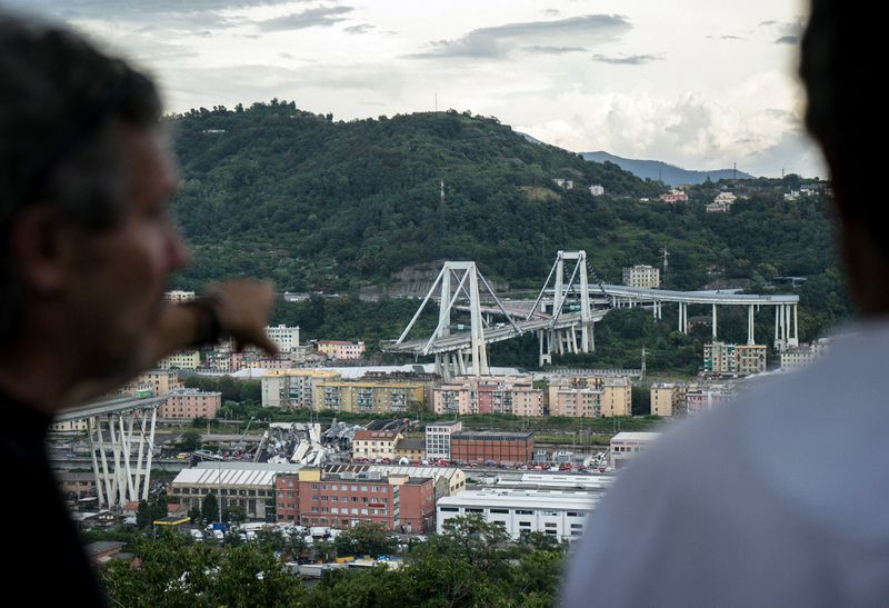 A view of the Morandi Bridge from afar shows the large middle section of the bridge missing.