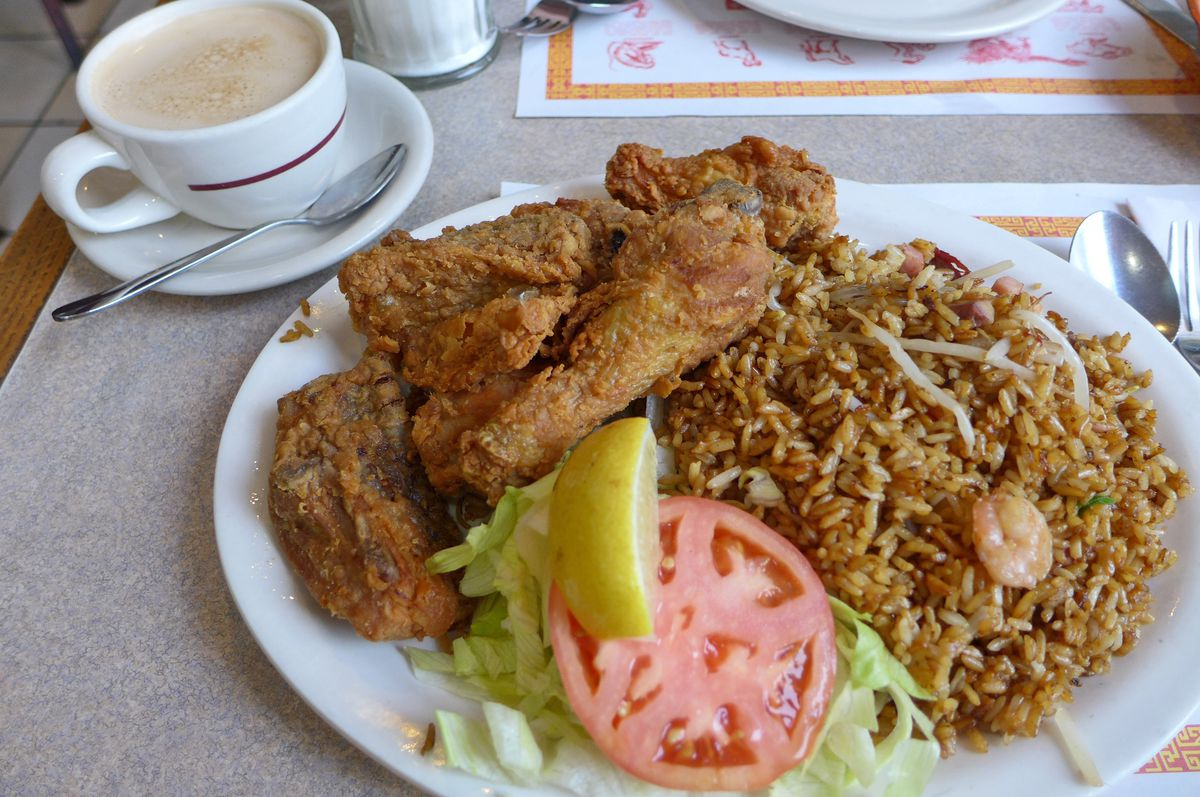 A plate of fried chicken with fried rice, plus a cup of coffee with steamed milk.