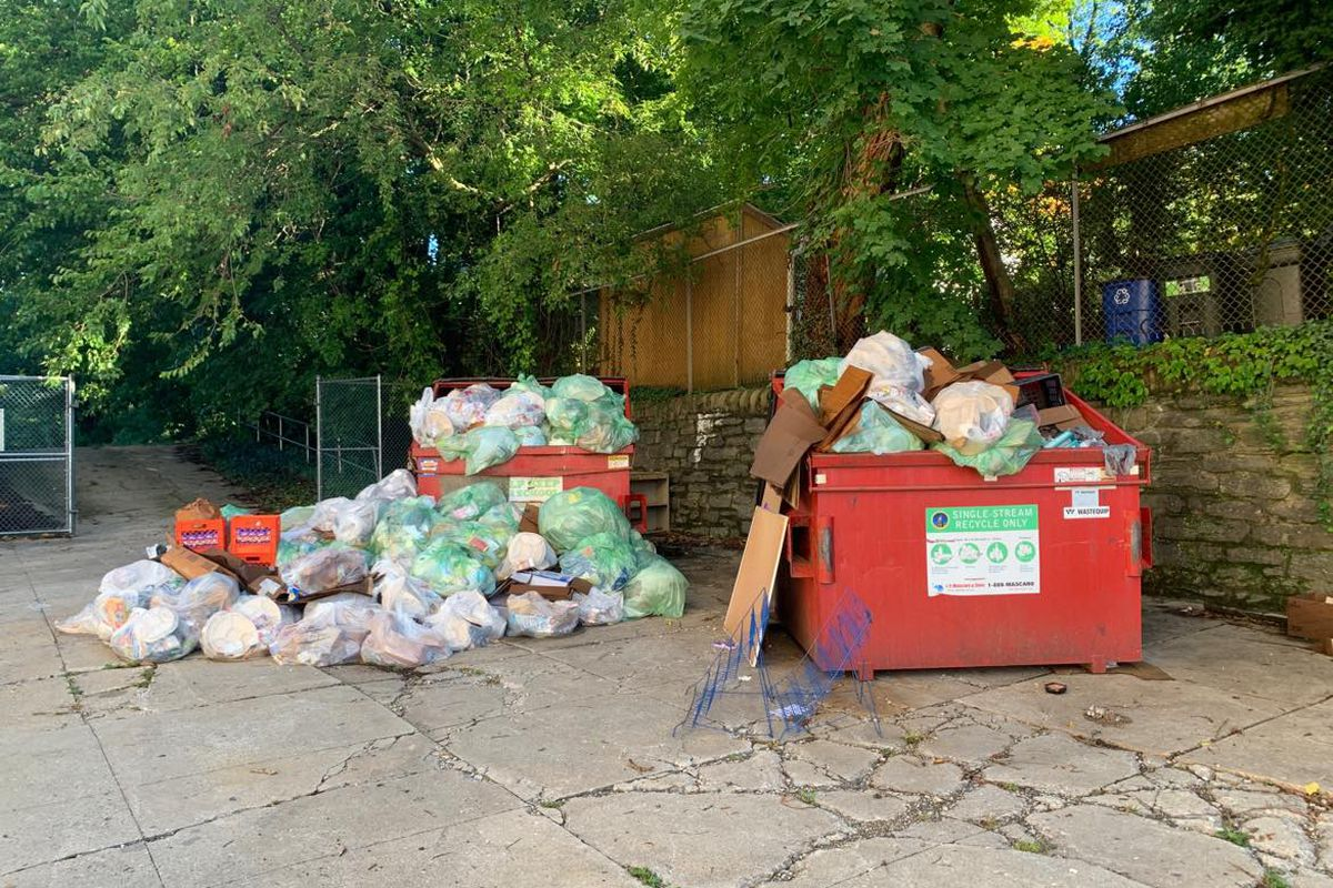 Dozens of trash bags sit next to a red dumpster filled with more trash bags.
