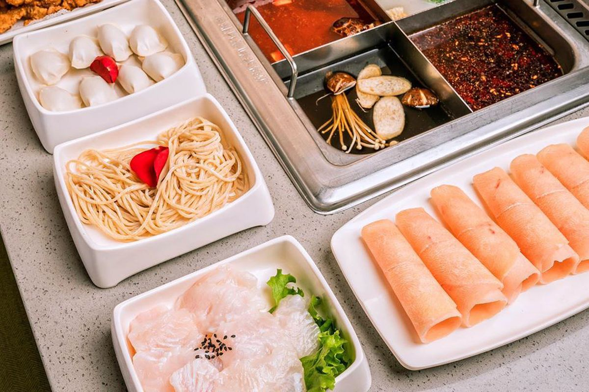 A four-chambered hot pot filled with colorful broths. Plates of thinly sliced meat and vegetables sit on the side.