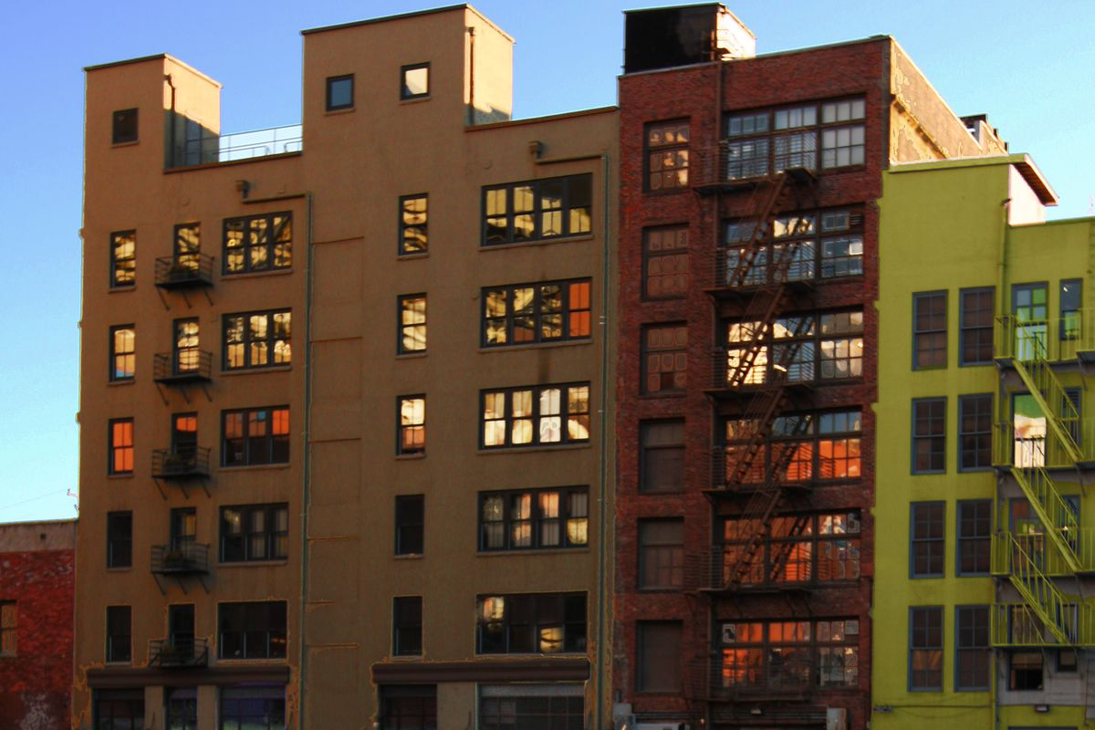 Three buildings with fire escapes, one tan, one brick, and one green, right up against one another