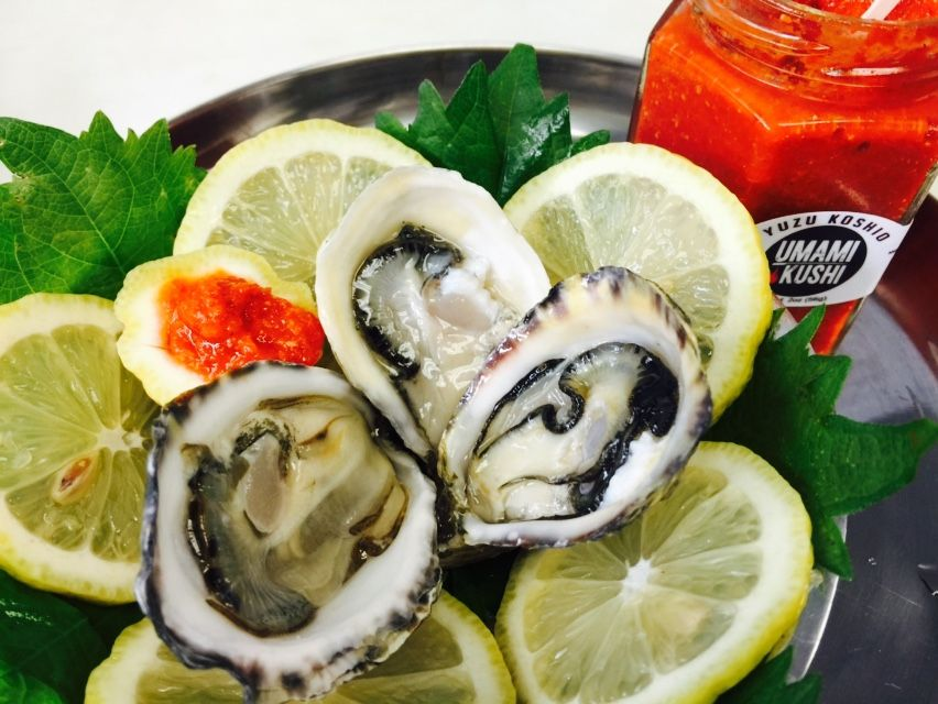 A closeup of oysters at Seattle Fish Guys surrounded by sliced lemons, with a bottle of a red drink labeled Umami Kushi
