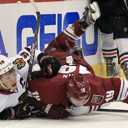 Phoenix Coyotes' Shane Doan, right, checks Chicago Blackhawks' Jonathan Toews, left, into the boards during the second period in Game 1 of an NHL hockey Stanley Cup first-round playoff series, Thursday, April 12, 2012, in Glendale, Ariz.