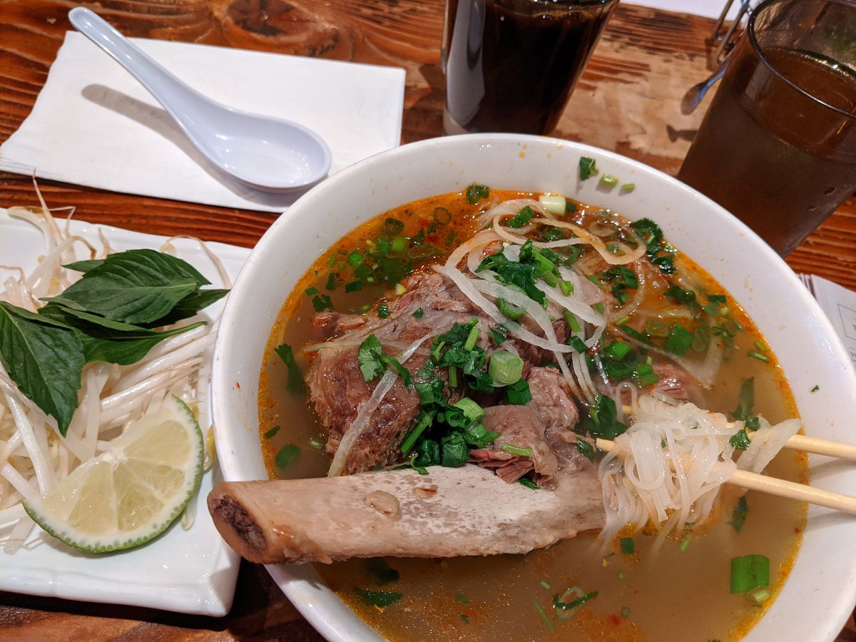 A giant beef rib sits in the middle of this bowl of pho.