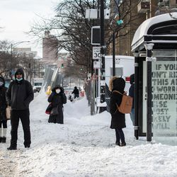 Commuters wait for the bus in the Edgewater neighborhood, Tuesday morning, Feb. 16, 2021, after a snowstorm dumped over a foot of snow in Chicago starting Sunday night. Snow is expected to continue to fall until Tuesday night.