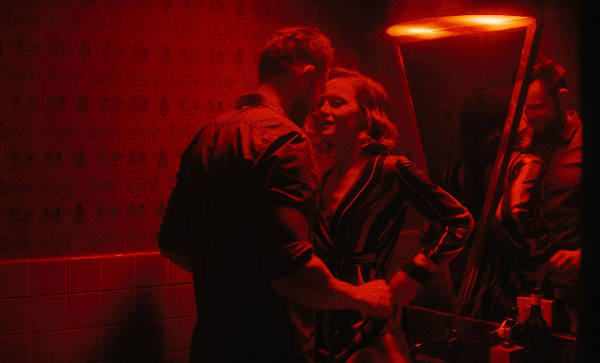 Under dim red lights, Joel McHale and Kerry Bishé make out in a bathroom in Happily
