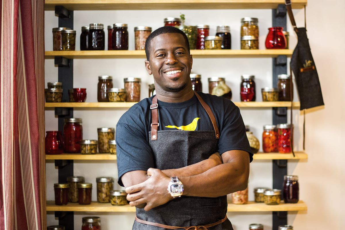 Chef Edouardo Jordan smiles in front of some shelves with pantry items.