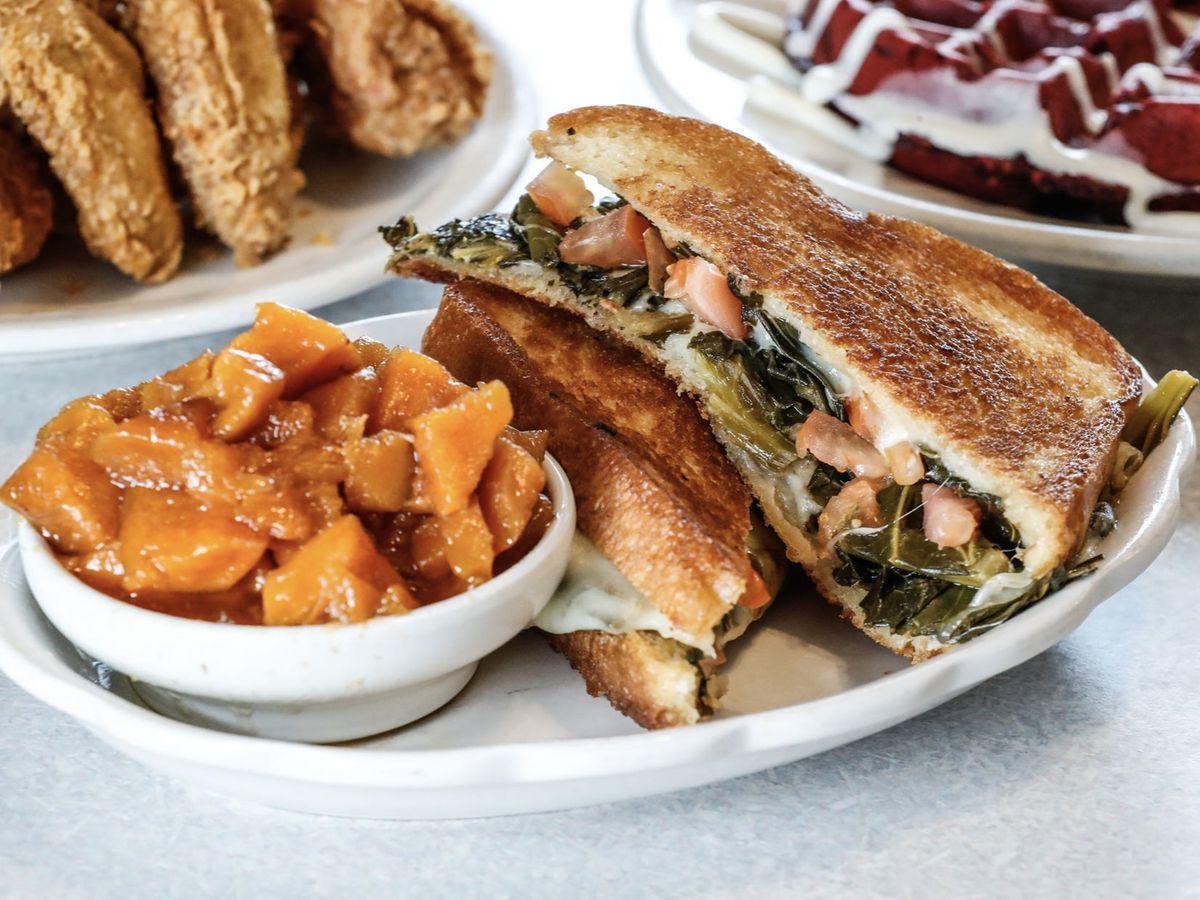 A thick grilled cheese, sliced in half and stacked on a plate beside a bowl of chunks of candied sweet potato. The sandwich bursts with collard greens, diced tomato, and cheese