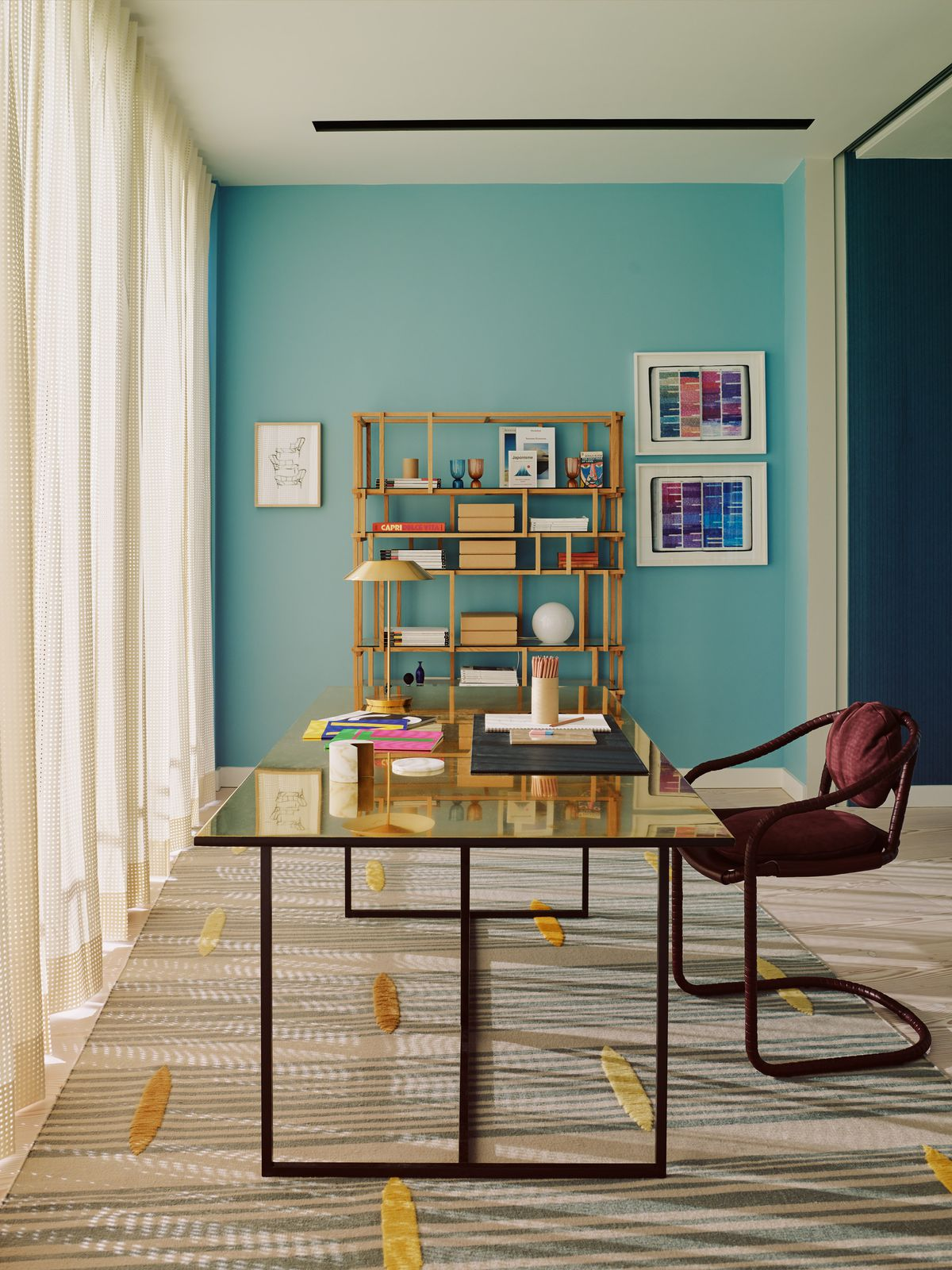 Home office with blue-green wall and sleek modern desk.