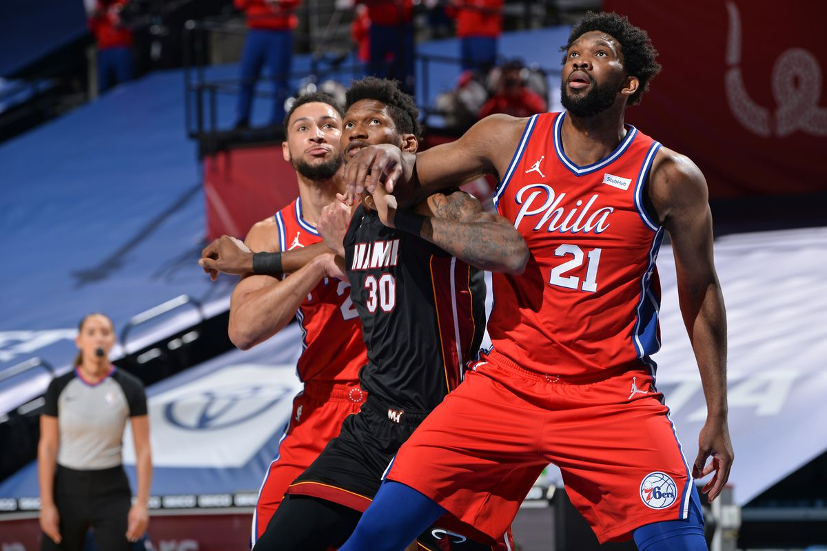 Chris Silva of the Miami Heat and Joel Embiid of the Philadelphia 76ers fight for the rebound on January 14, 2021 at Wells Fargo Center in Philadelphia, Pennsylvania.