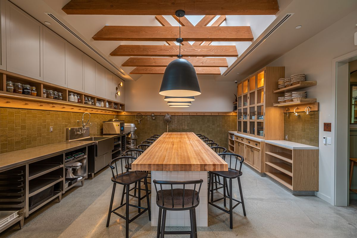 A long wooden table for prepping food inside a restaurant, surrounded by equipment and with a tall skylight at top.