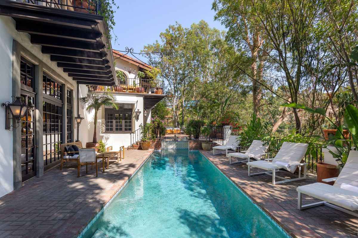Lounge sets next to a long rectangular pool. A house with tile roof is nearby.