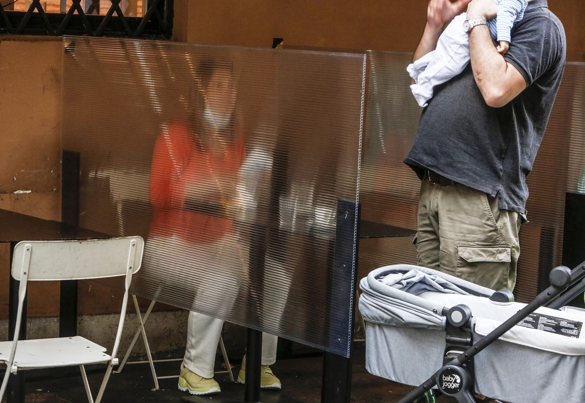 Woman seated at an outside restaurant table behind a large seat of plexiglass.
