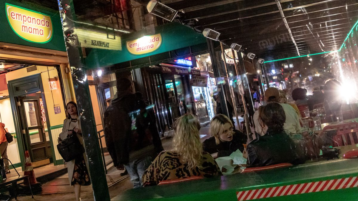 Patrons sit at outdoor tables on Ninth Avenue at Empanada Mama, whose green, yellow, and red awning sits above the street
