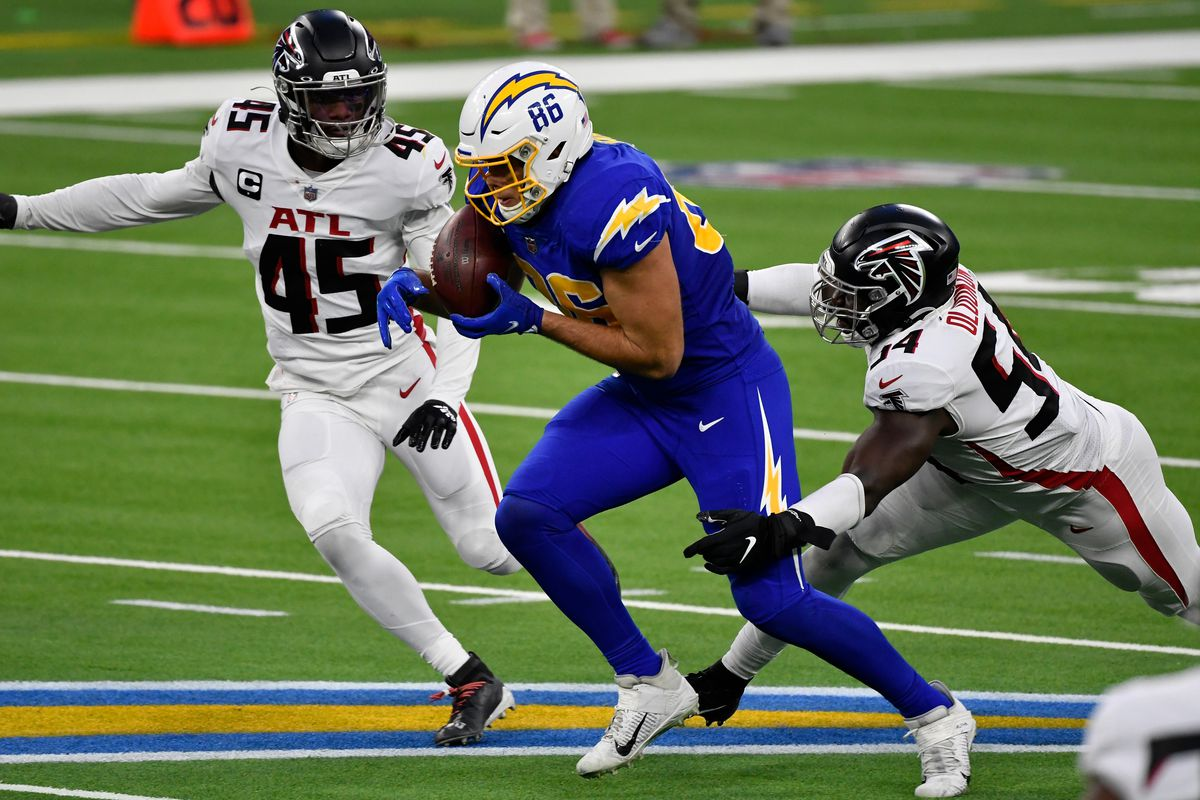 Los Angeles Chargers tight end Hunter Henry (86) catches a pass and tries to break away from Atlanta Falcons linebacker Foye Oluokun (54) and Atlanta Falcons linebacker Deion Jones (45) in the fourth quarter at SoFi Stadium.