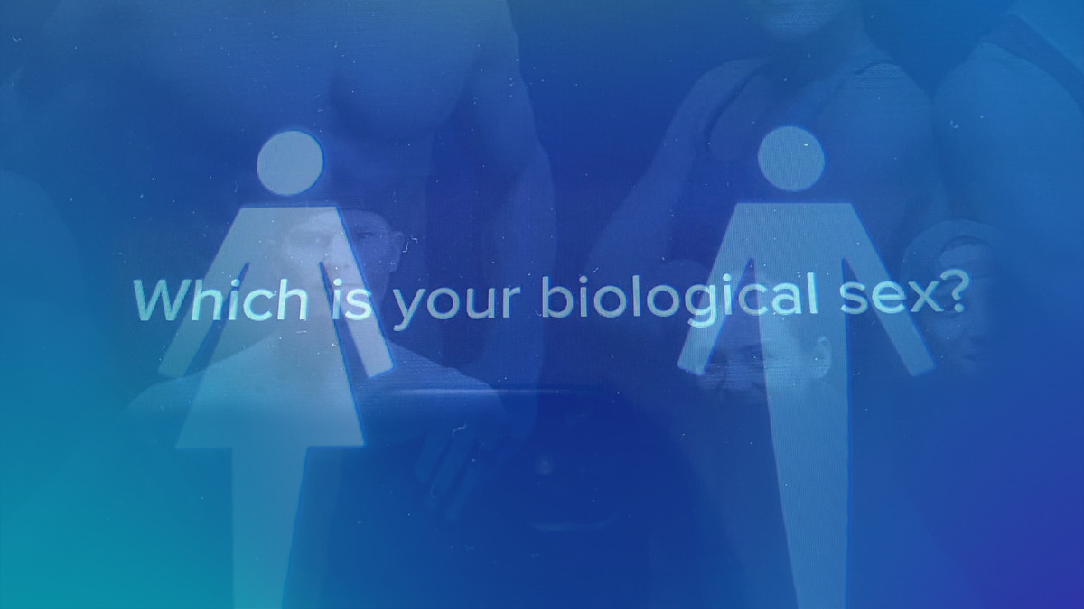 """On screen display shows a figure representing female and male bodies and words that say """"Which is your biological sex?"""""""