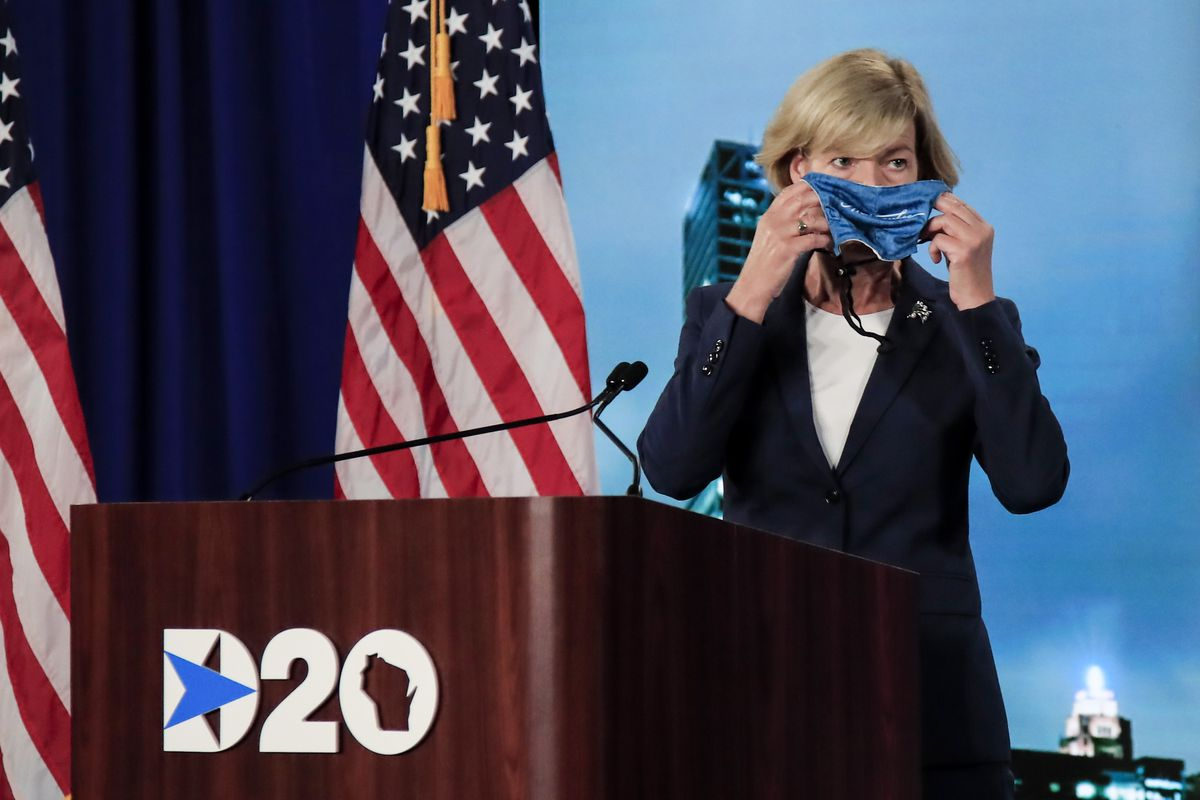 Senator Tammy Baldwin holding a mask to her face while at the Democratic National Convention podium.