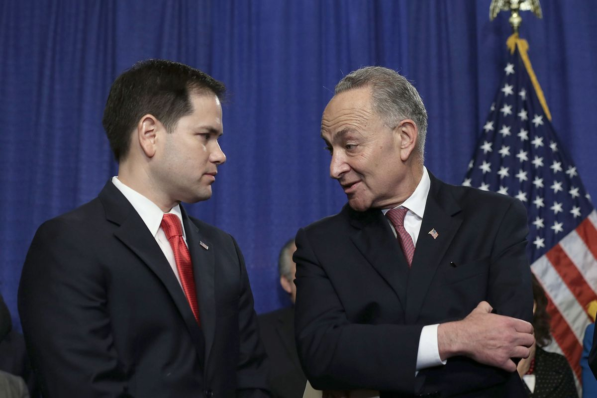 Sen. Marco Rubio (R-FL) listens to Sen. Chuck Schumer (D-NY) during a news conference in 2013.