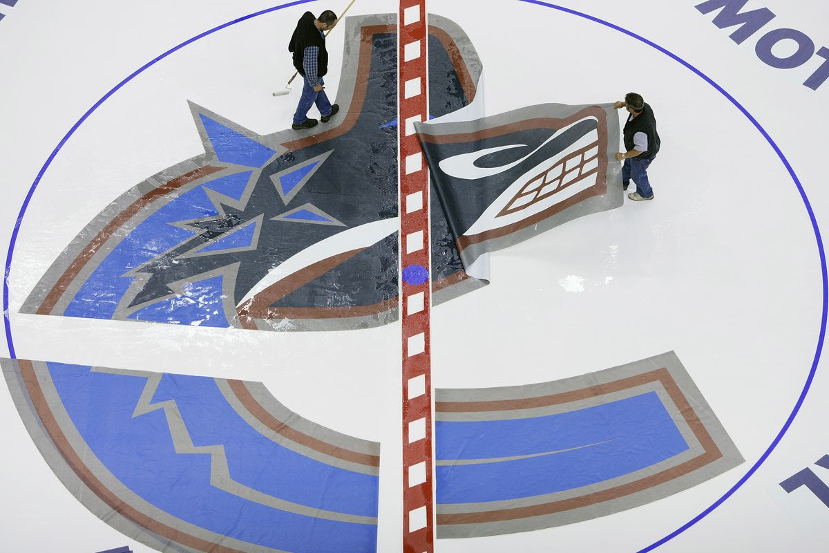 The ice crew installs the Vancouver Canuck logo in the freshly created ice at General Motors Place in Vancouver, Canada on August 4, 2005.