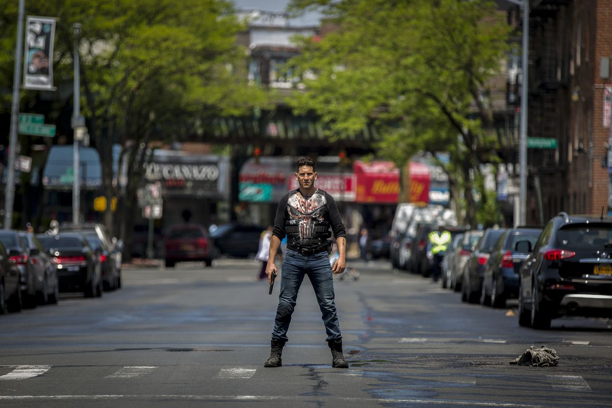 Jon Bernthal as The Punisher standing in the middle of a New York street with a bloody t-shirt