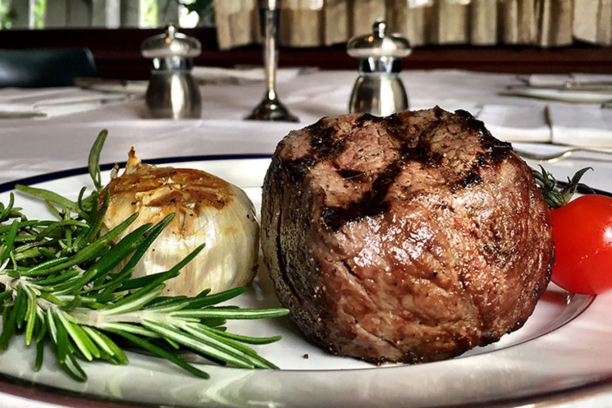 A thick cut baseball steak sits cooked on a white plate next to some garlic and rosemary.