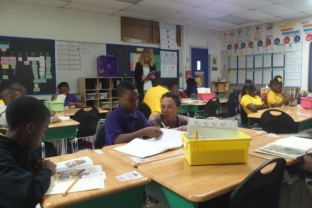 Aspire CEO Carolyn Hack talks with a student at Hanley 1 Elementary School during her tour of Aspire-operated charter schools in Memphis.