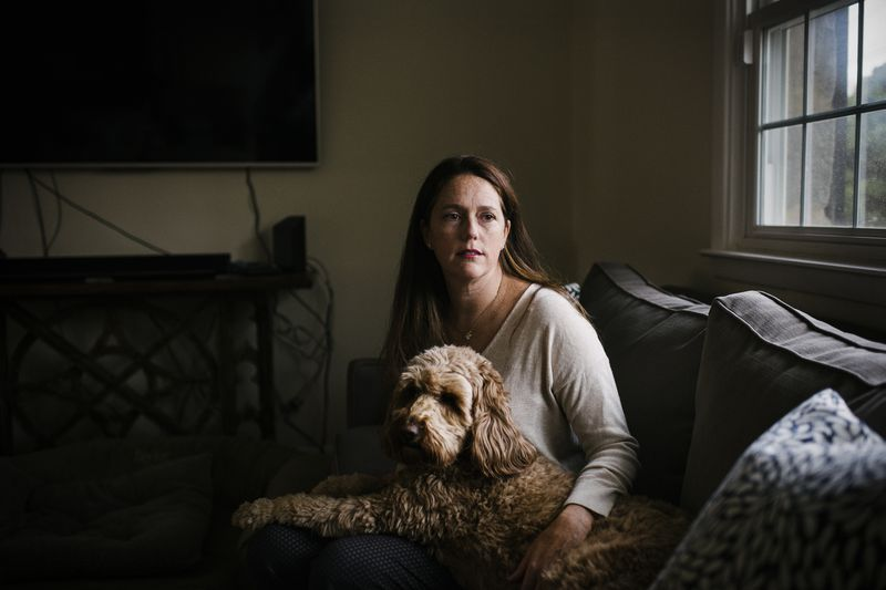 Allison Gamba siting in her living room with her dog.