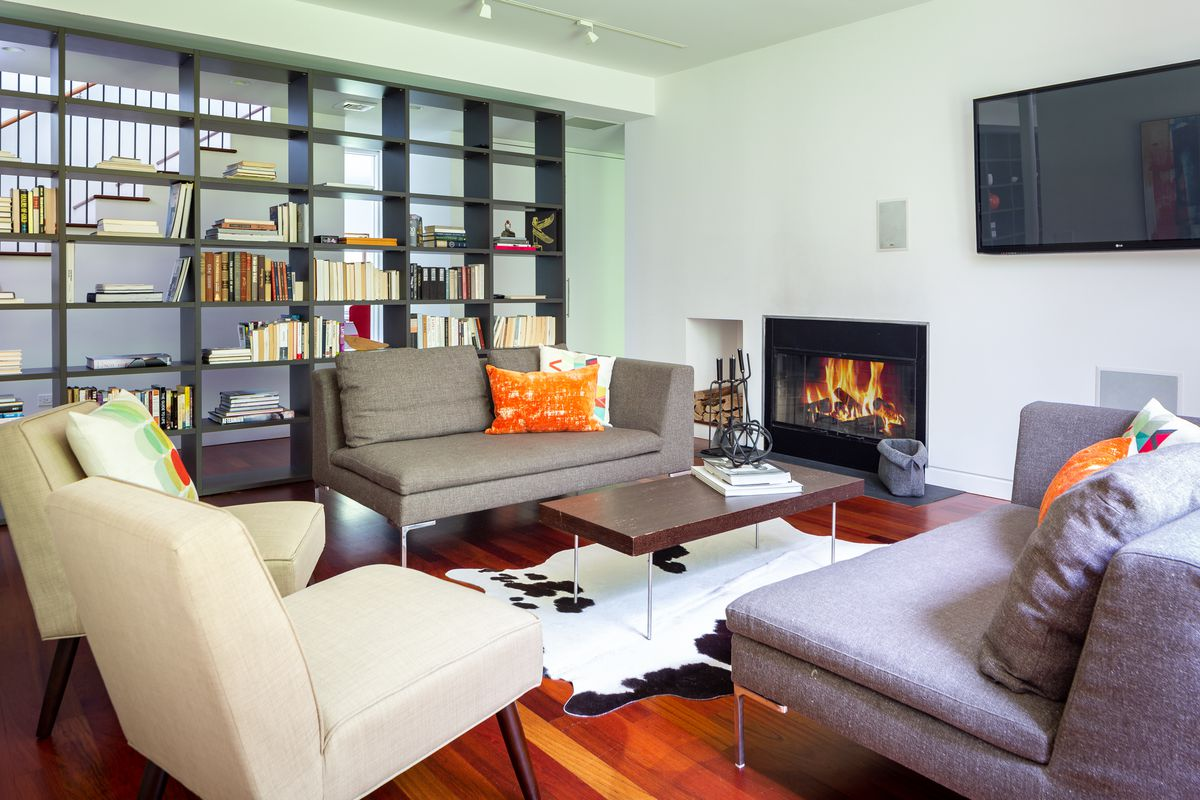 A living room features a fireplace with contemporary sofas and lounge chairs around it. An open bookshelf sits in the back as a room divider.