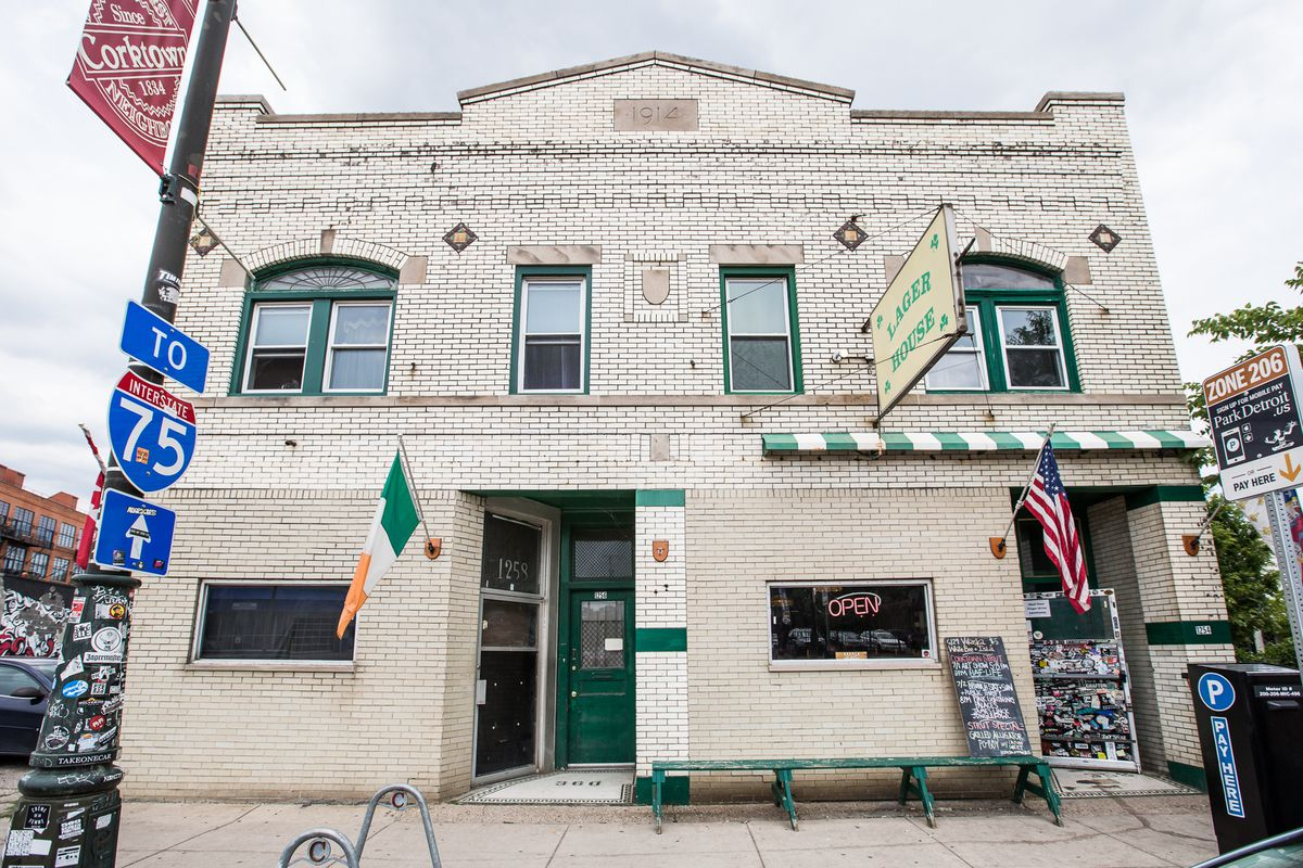 The white brick exterior of PJ's Lager House on a cloudy day. An Irish flag hangs near the door.