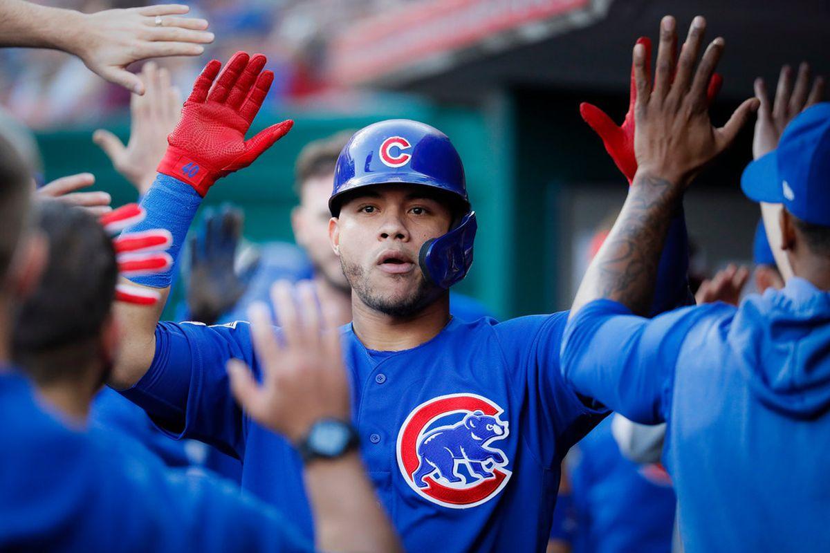 Wilson Contreras high-fives teammates in the Cubs' dugout.