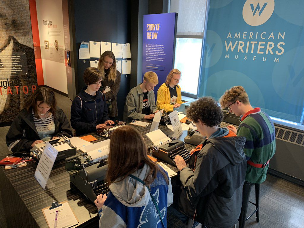 A group of students seated at a table typing stories