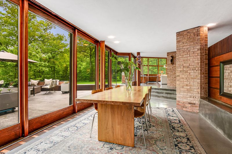 A wooden dining room table sits on a rug next to large windows that look onto a patio.