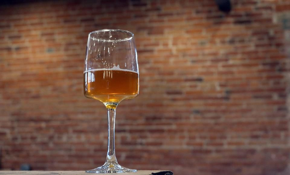 Specialty glass of beer against a brick wall