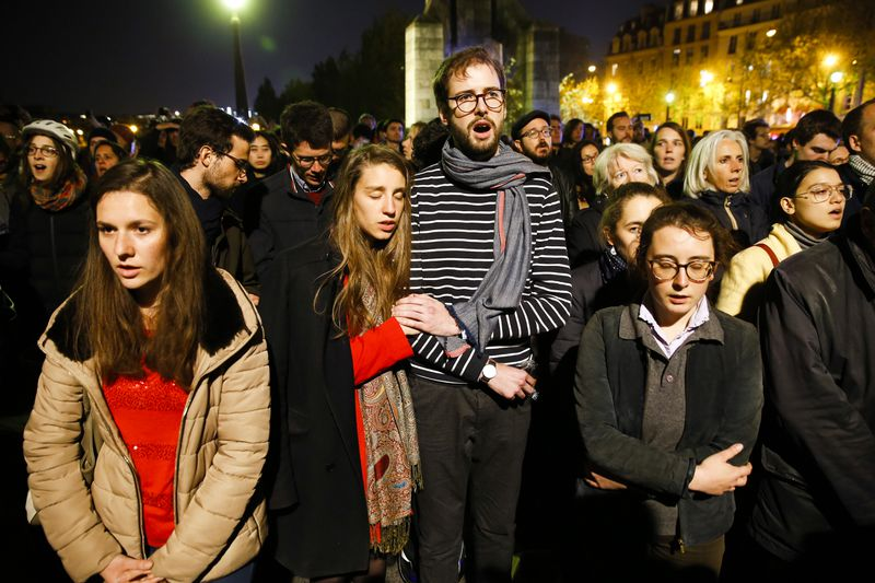 Parisians gather next to the cathedral to pray as the structure burns.