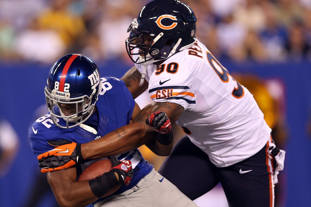 EAST RUTHERFORD, NJ - AUGUST 24:   Julius Peppers #90 of the Chicago Bears shoves Rueben Randle #82 of the New York Giants during a preseason game on August 24, 2012 at MetLife Stadium in East Rutherford, New Jersey.  (Photo by Elsa/Getty Images)