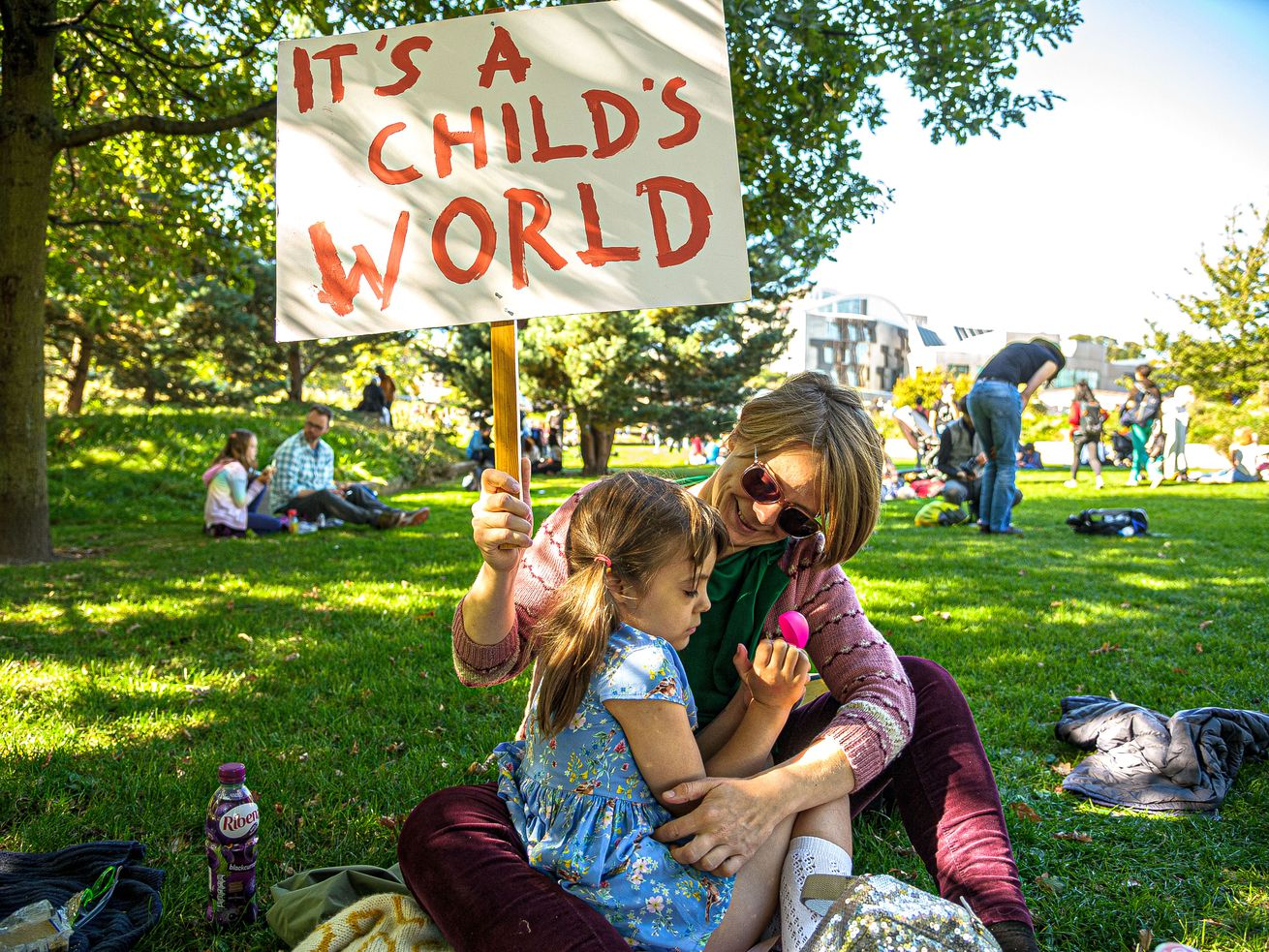 """A mother embracing her daughter holds a placard that says """"It's a child's world"""" at the March through Edinburgh, part of the global climate strike movement."""
