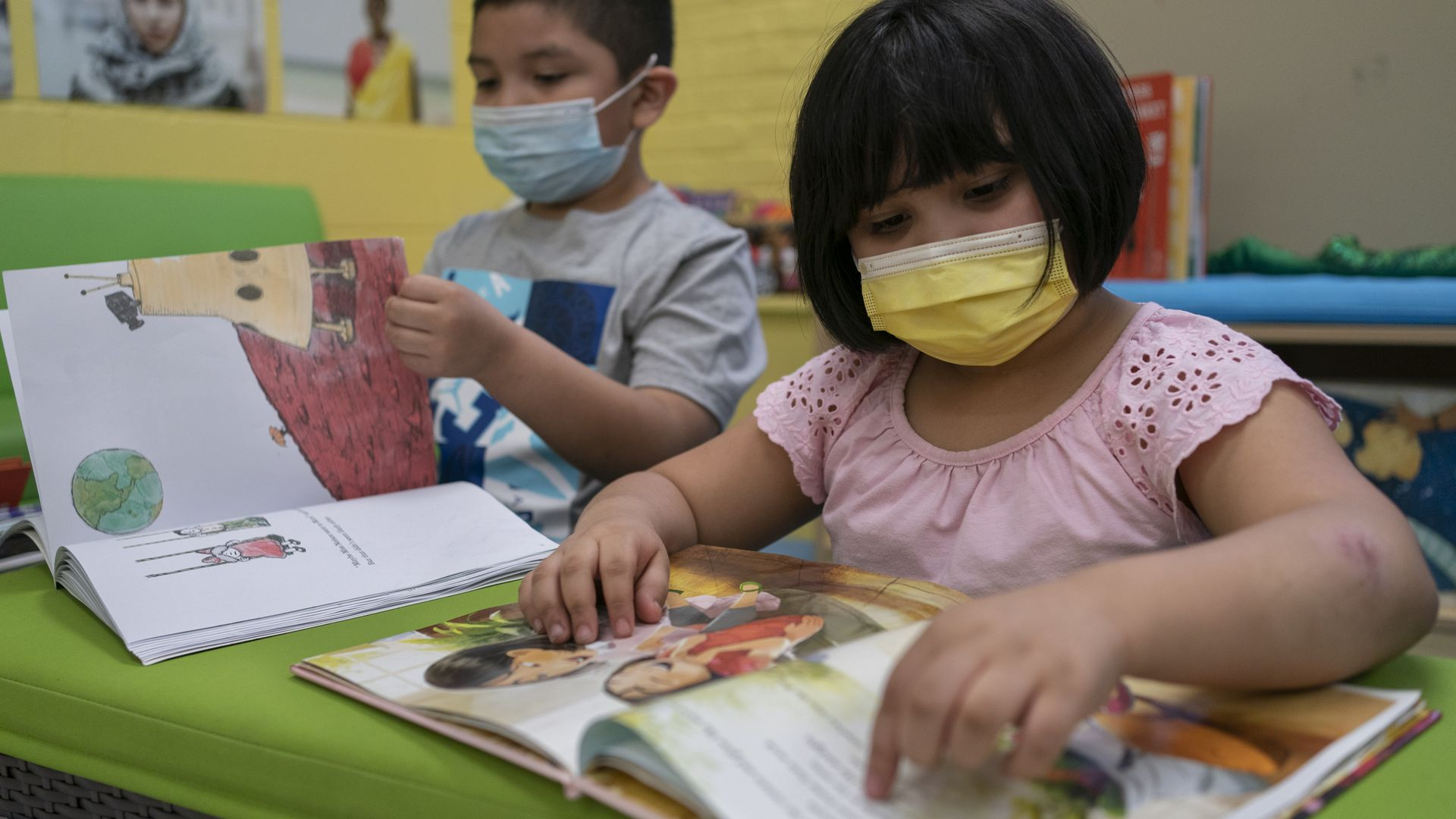 To the left, a young boy wearing a blue face mask and a gray shirt looks at a book. To his right is a young girl with a yellow face mask and a pink shirt looking at another book.