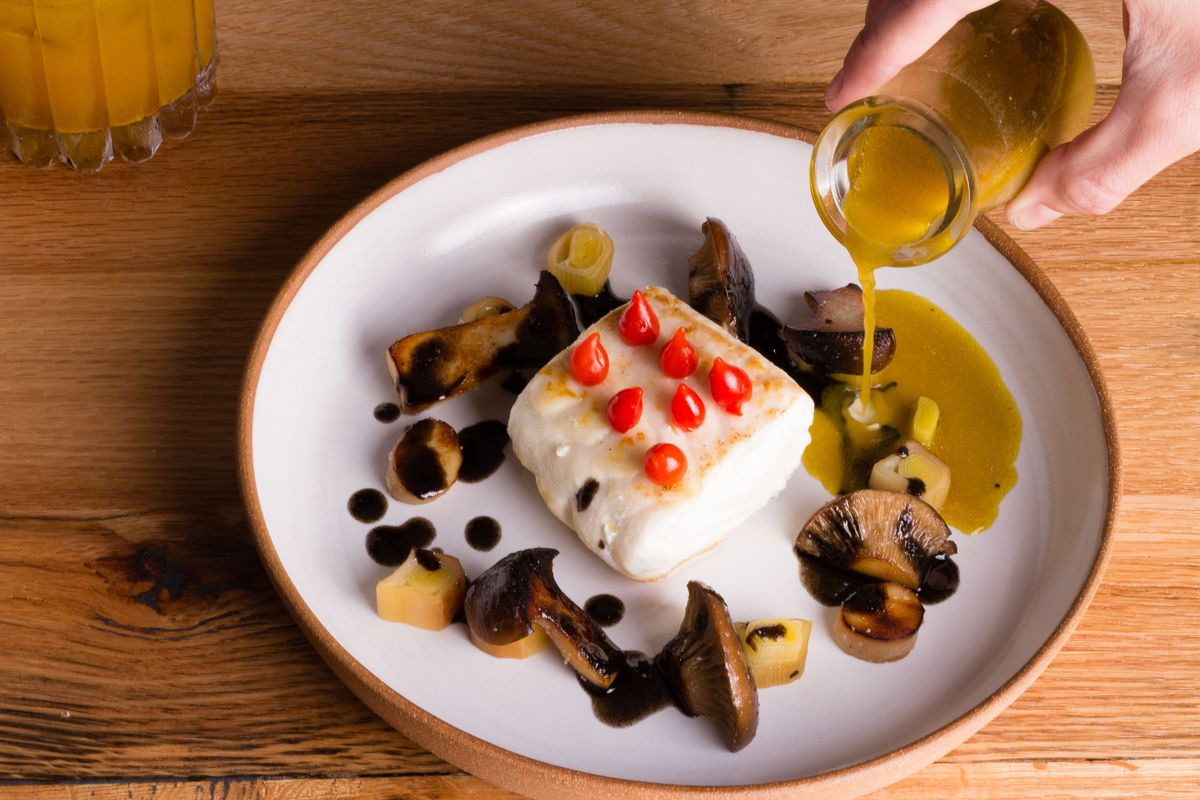A halibut steak with seven tiny red peppers on top and mushrooms encircling the halibut on a plate. A hand pours sauce from a jar onto the plate.