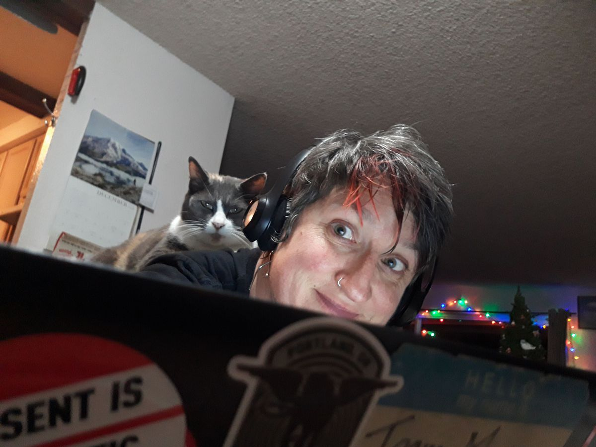 Team mom at her computer with Calico cat Tiptoe on her shoulder.