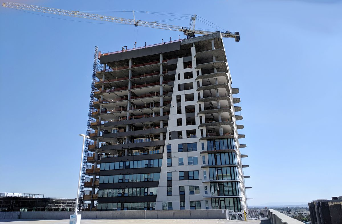 A photo of a high-rise that is about half complete. Half the exterior windows and walls are installed.